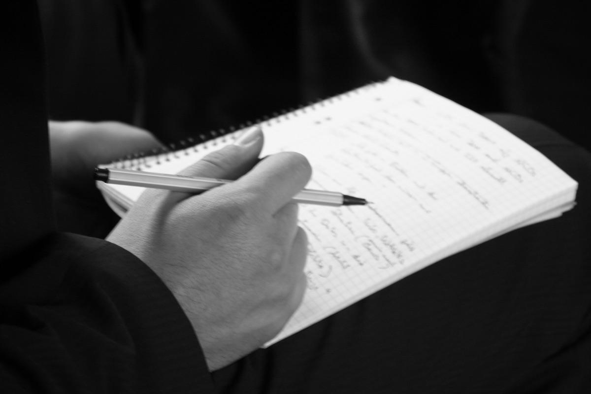 Eine Hand und ein großes Notizheft © Tom Rübenach